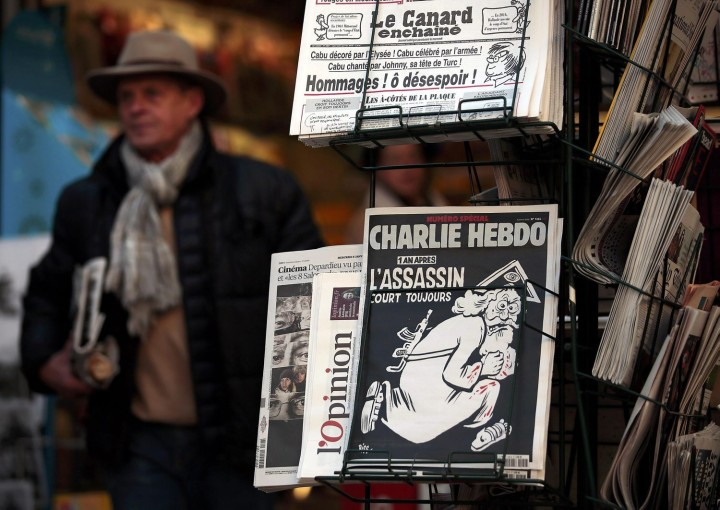 "A copy of the latest edition of French weekly newspaper Charlie Hebdo with the title ""One year on, The assassin still on the run"" is displayed at a kiosk in Nice, France, January 6, 2016. France this week commemorates the victims of last year's Islamist militant attacks on satirical weekly Charlie Hebdo and a Jewish supermarket with eulogies, memorial plaques and another cartoon lampooning religion. REUTERS/Eric Gaillard FRANCE-SHOOTING/ANNIVERSARY"